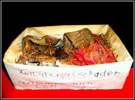 """""""In Memoriam Amselfeld"""" / """"Kolateralschaden verursacht durch Luftschlag"""" / """"Hier ruht die zertrümmerte Seele des Joschka F."""" WVZ 6, entstanden während des Balkankrieges 1995 - ergänzt 1999. Mit Klopapier umwickelter Schuhkarton, gefüllt mit Materialien."""