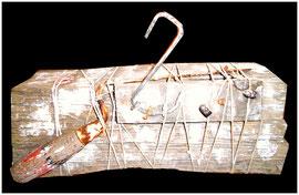 """""""Auf Holzschiffchen reitende Drahtente rammt treibholzführende Zungenkelle, trotz Dichtungsring"""" Gestringen, 11/1992, Werkverzeichnis 327, Brennholzskulptur für die Toleranz: Brennholzscheid mit Zungenkelle, Drahthaken, Dichtungsring, Latte, Schnüre, Näge"""