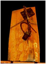 """""""Die Kreuzigung"""" / Werkverzeichnis 1.790 / datiert 11/1998 / Maße: maximale Breite 17,0 cm / maximale Höhe 35,9 cm Eisen, Schnüre, Metallfedern, Schraubenmutter und diverse andere Materialien auf Brennholzscheid"""