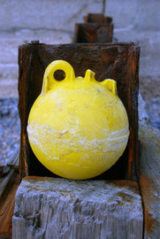 Yellow float with one handle reminding me of an early Cypriot clay water bottle