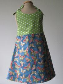 Achter: Butterfly jurkje met zakjes. Het jurkje wordt op de schouders gestrikt. Artikelcode 98/104-040.