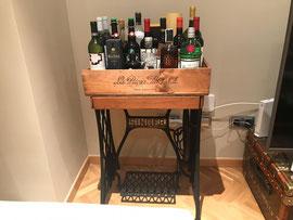 Mueble bar realizado con el pie de una máquina de coser y una caja de vino.