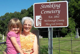 Sue Frakes, trustee of the Stoneking Cemetery, holding her great granddaughter Daylynn Alexander, accepts a new sign