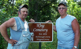 Darrell Roberts (left), current property owner, and Carol Gooden, former owner, accept a new sign for the King Cemetery.