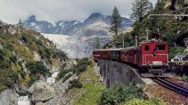 Lok 34 nahe Gletsch mit dem Rhonegletscher auf der Furka Bergstrecke kurz vor der Stilllegung der Strecke (1981)