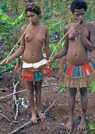 PNG, Trobriand Islands: two Kapwani girls (Yabitaula, left, and Iboila, right) playing flutes made from papaya fruit stems