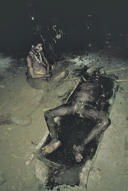 PNG: Sodhu's rotting body lying in the communal living area of Unawobi longhouse 9 days later (his wife sits by the corpse)