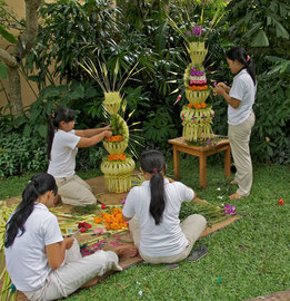 Bali, Ubud: girls at the Kamaneka hotel preparing decorations (janur) from coconut leaves and flowers