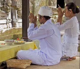 Bali: a Pemangku (priest) and his assistant praying at Gunung Kawi Temple