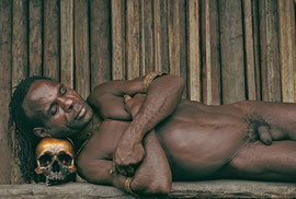 W. Papua, Asmat: Otor, a man of Wares village, sleeping on a trophy skull with red seeds set in the eye-sockets