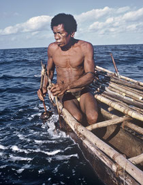 PNG, Trobriand Islands: Kasiyotagina, chief of Yuwada village, uses a coconut shell rattle to attract sharks