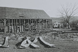 A side view of the barn frame, with discarded roof panels in foreground (Stanton Hall on the far right)