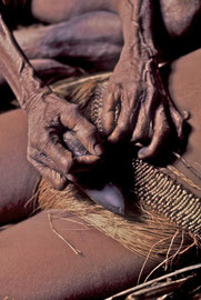 W. Papua, Asmat: an elderly 'midwife' uses a sharp shell to sever the girl's cane umbilical cord knotted around around the stone axe-head attached to her waist
