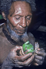 PNG, Southern Highlands: Hungeru, a Huli sorcerer, spits and mutters a spell over a magic bundle