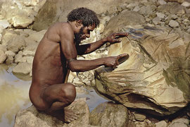 W. Papua, Baliem Valley: a Dani tribesman sharpens his stone adze-head on a boulder in a stream bed