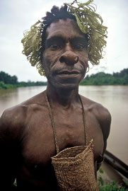 W. Papua, Asmat: a warrior from Tjemor village wears a bag on his chest, indicating he may be about to participate in a headhunting raid