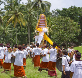 Bali, Payangan: Pelebon cremation ceremony. The gambelan musicians escort the 'bade' into the cemetery grounds