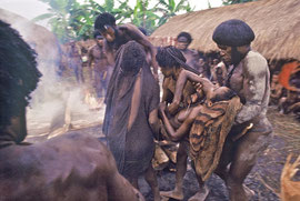 W. Papua, Baliem Valley: the dead girl is carried from her hut and placed on a funeral pyre