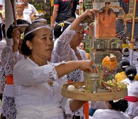 Bali, Ubud. women sprinkling purifying water at Odalan ceremony at Pura Dalem Kedewatan temple