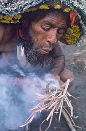 PNG, Southern Highlands: as Degondo blows on a glowing spark the grass finally catches fire