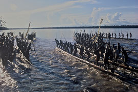 W. Papua, Asmat: parade of 17 war canoes (Ti-mbadn) from the villages of Erma, Sauwa, Sona, Momogo & Bu on the Pomatsj river