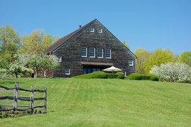 The barn in May 2013, flanked by blossoming fruit trees (the fence in the foreground encloses our vegetable garden)