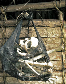 PNG: Nomad River: a billum (net bag) containing the bones of a deceased Biami hangs within an abandoned longhouse
