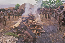W. Papua, Baliem Valley: the dead girl's mother wails as smoke rises from the pyre