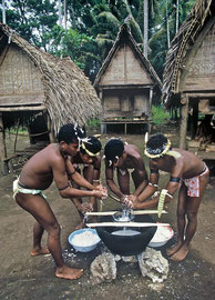 PNG, Trobriand Islands: Kapwani villagers prepare a dish of 'mona', made from yams, shredded coconut and coconut milk