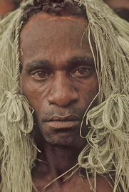 W. Papua, Asmat: another of the three men from Wares, decorated with strips of sago palm fronds for the 'Tasor Juwi' adoption ceremony in Basim