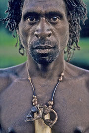 W. Papua, Asmat: Awun, a man from Wares village, wears a necklace of two human vertebrae and section of bamboo indicating he has previously taken a head