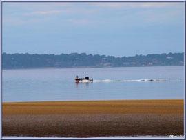"""Bâteau sur le Bassin partant à la pêche, vue depuis le front de mer de la plage Péreire en """"Ville de Printemps"""" à Arcachon"""