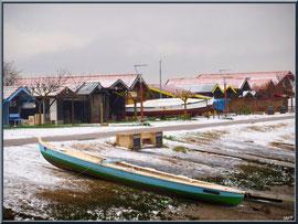 Les cabanes et un canot en habit neigeux