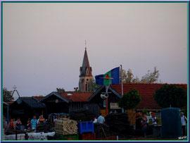 Le drapeau de Gujan flotte au vent et derrière le clocher de l'église, en fin d'après midi