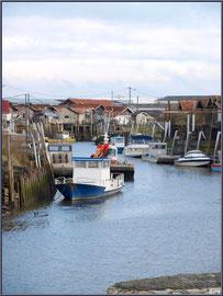 Un chenal du port, bateaux et cabanes