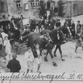 """Bild vom ersten Weinfest in Oberschwarzach aus dem Jahr 1949. Der Umzug mit dem geschmückten Kutschgespann zieht hier gerade auf der Hauptstraße vor der Gastwirtschaft """"Zur Traube"""" vorbei."""
