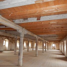 Auch der dritte Lagerboden wartet noch auf Ideen. Wie im Bild zu sehen ist, mussten erhebliche Teile des mächtigen Gebälks bei der Renovierung ausgetauscht werden. Ursachen waren eindringende Feuchtigkeit und Überlastung bei der Nutzung als Lagerhaus.