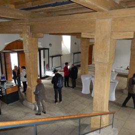 Die Eingangshalle wird dominiert durch die mächtigen Stützpfeiler aus Holz. Mit der Thekenanlage ist sie auch gastronomisch nutzbar.