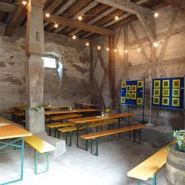 """In der hergerichteten Scheune ließ es sich gemütlich sitzen. Im Hintergrund Schautafeln zum Projekt """"Farbe"""" der örtlichen Schule."""