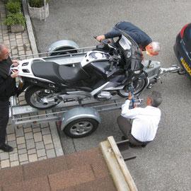 Sogar im weißen Hemd ist sich der Konrad nicht zu fein, um beim Aufladen eines Motorrades zu helfen - Morgens Abfahrt der Holländer