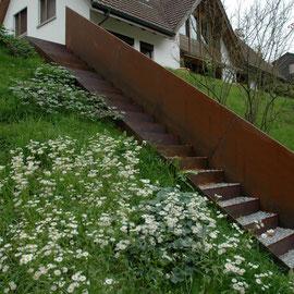 Stahltreppe in Böschung versetzt, Tritte mit Kies aufgefüllt.