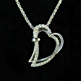 AN 57 - 14K white gold heart shaped pendant with diamonds.