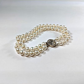 A 94 - double strand pearl bracelet with sterling filigree clasp.