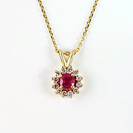 AN 72 -14K yellow gold pendant with center ruby and a halo of diamonds.