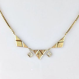 AN 99 - 14K yellow gold necklace with triangle shapes and diamond accents.