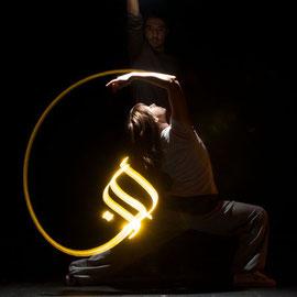 Derrière la danseuse, on peut voir Kaalam effectuant une chorégraphie lumineuse.