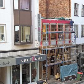 Auf diesem Foto sieht man noch im oberen Stock die alte Fassade in rot und unten bereits neue Elemente.
