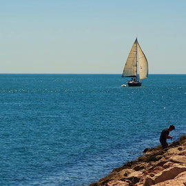 am Ufer des Guadiana in Vila Real de Santo Antonio ... ein Angler geht in Ruhe seiner Tätigkeit nach und ein Segelboot verlässt die sicheren Ufer des Flusses und segelt hinaus auf offene Meer