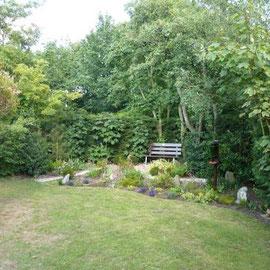 ein Teil vom großen eingezäunten Garten mit Gartenbank