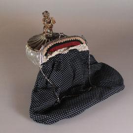Bolso en tela color negro con lunares blancos.
